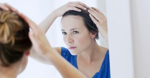 Woman checks in the mirror if her hairline is receding.