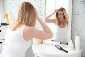 Woman looking in mirror concerned about thinning hair.