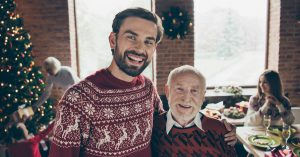 Elderly balding father and son with full head of hair wearing Christmas sweaters by the tree.