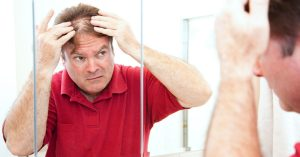 man looking at his thinning hair in the mirror