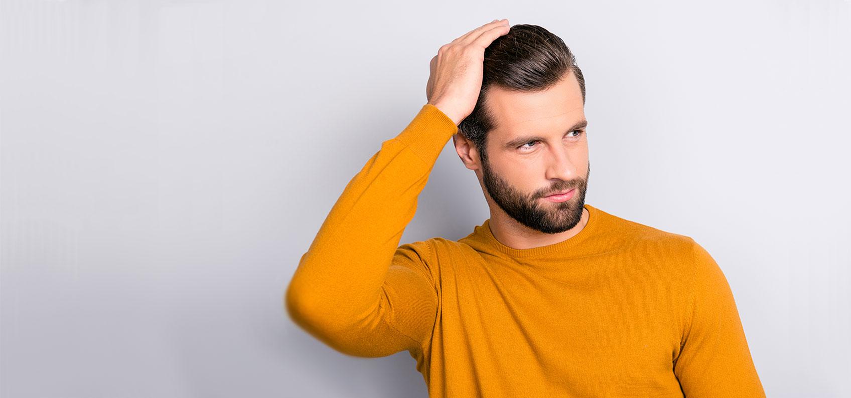Man running hands through hair robotic hair restoration