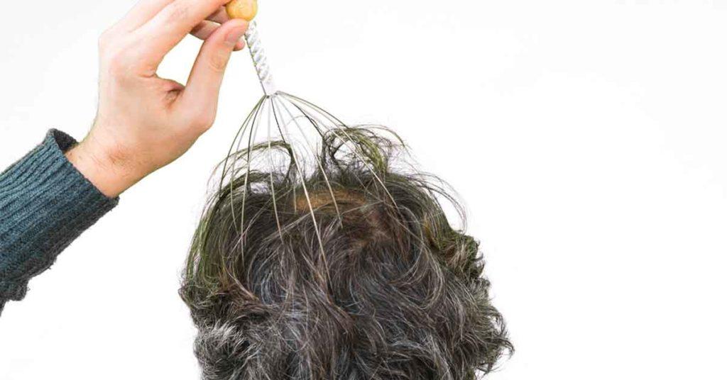 man giving himself a scalp massage